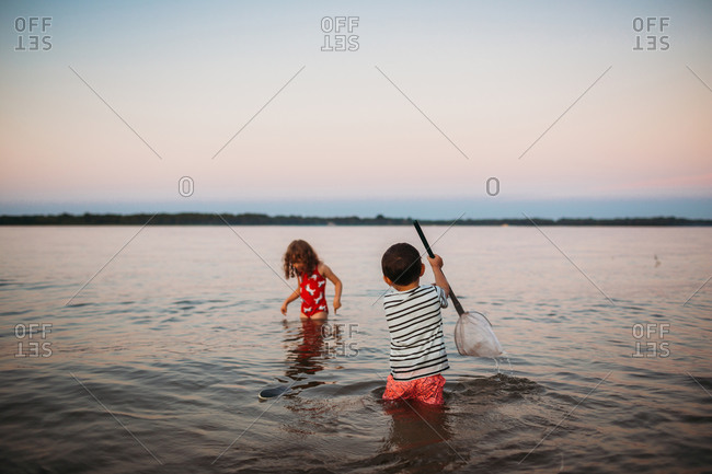 Young siblings trying to catch fish in lake at sunset