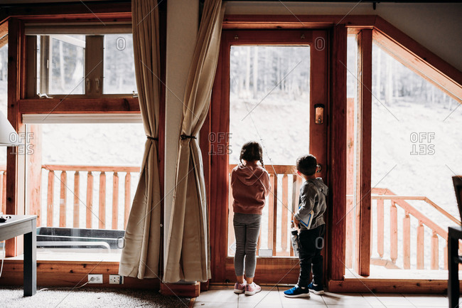 Young brother and sister looking out large cabin windows