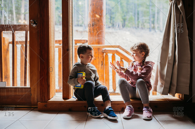 Brother and sister sitting in window sill at cabin