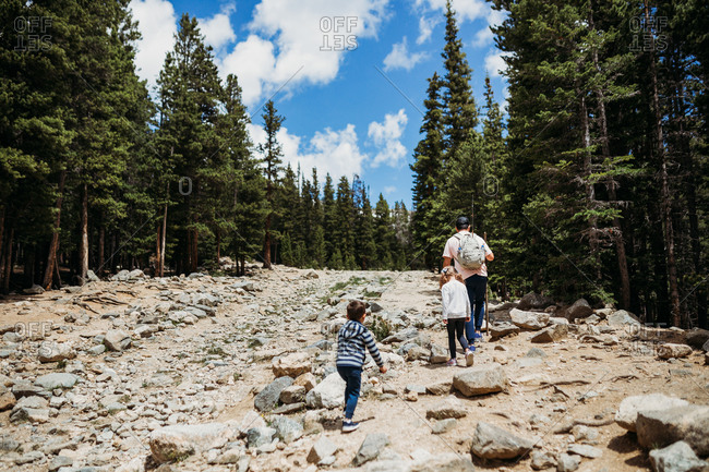 Dad and two kids hiking up large rocks on mountain