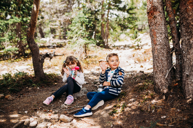 Young brother and sister taking a water break while hiking