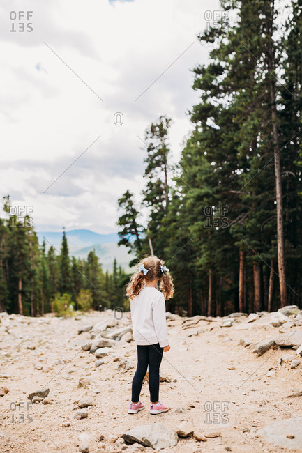 Young girl looking down mountain hiking trail in summer