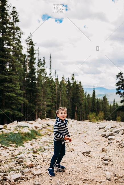 Toddler boy hiking down mountain in summer