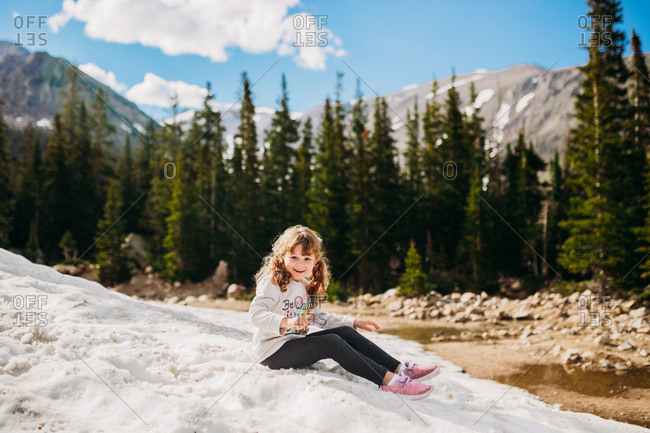 Happy young girl playing on snowy mountain