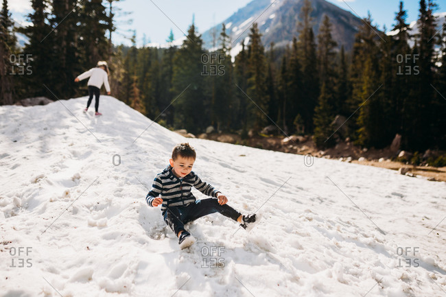 Happy toddler boy sliding down snow in the mountains