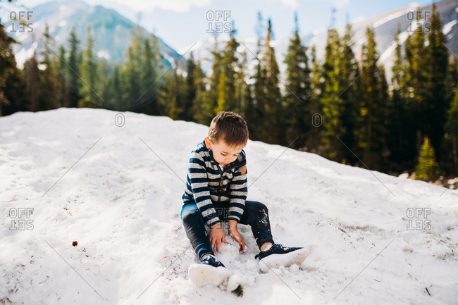 Young boy playing in snowy mountains in Colorado