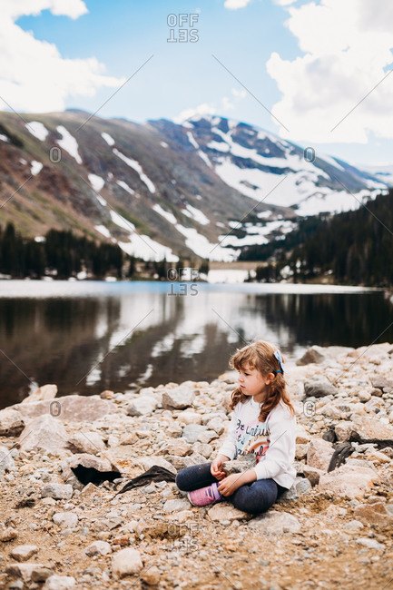 Young girl sitting on rocks near lake with mountain behind