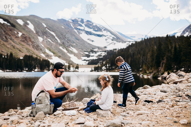 Father and two kids putting bait on fishing pole
