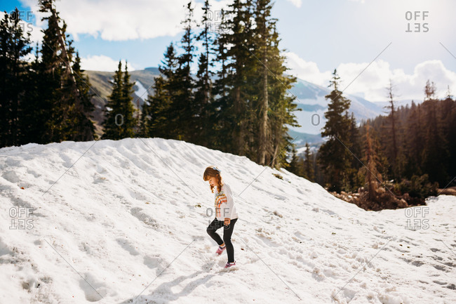 Young girl hiking through snowy mountains on a sunny day