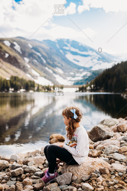 Young girl sitting looking at lake near mountains