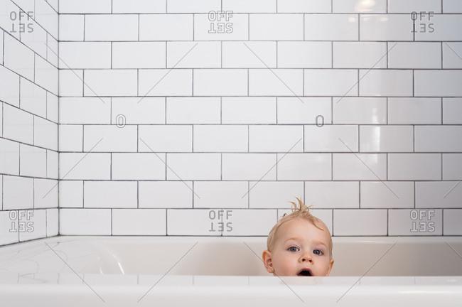 Little boy in bathtub with white subway tile surround