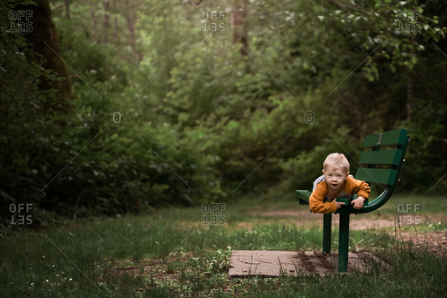 Toddler boy climbing on green bench at a nature park