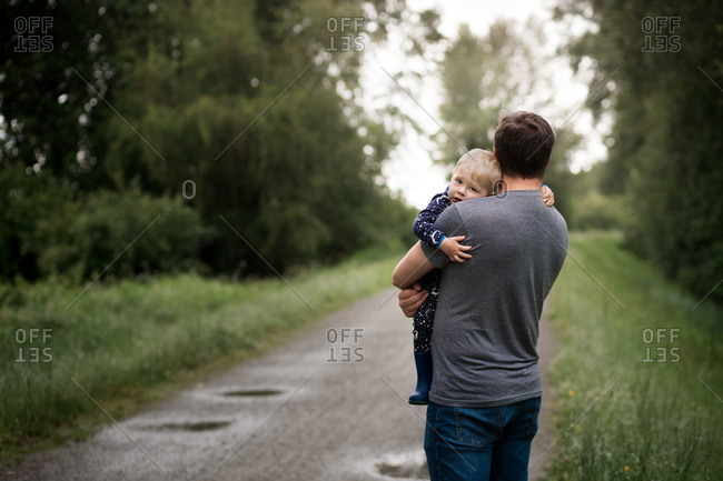 Father holding and comforting toddler boy on side of gravel path