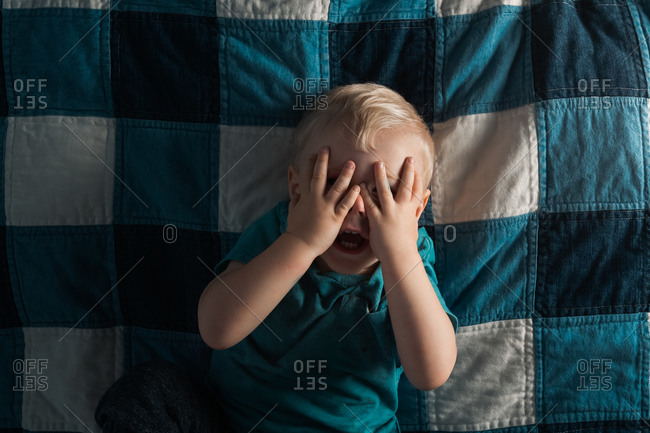 Overhead view of toddler boy playing peek-a-boo on bed