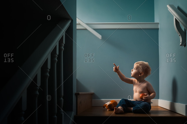 Little boy sitting on stair landing eating an apple and pointing up towards a light
