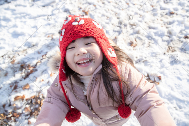 Happy little girl playing in the snow