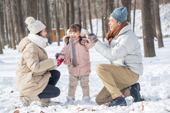 Family of three playing in the snow