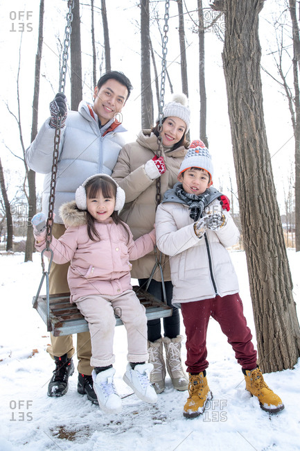 Happy family posing together by the swing