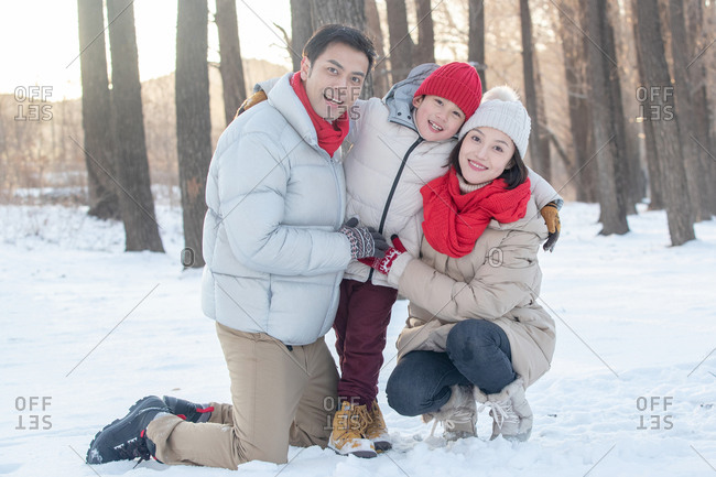 Happy family of three together in the snow