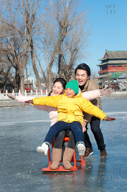 Happy family playing on the skating rink