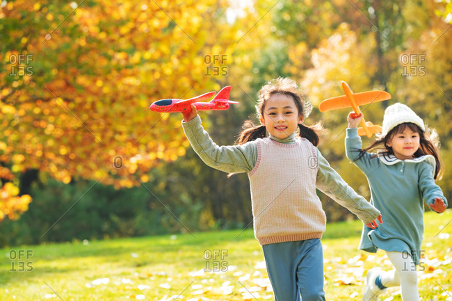 Girls play in the park with a toy plane