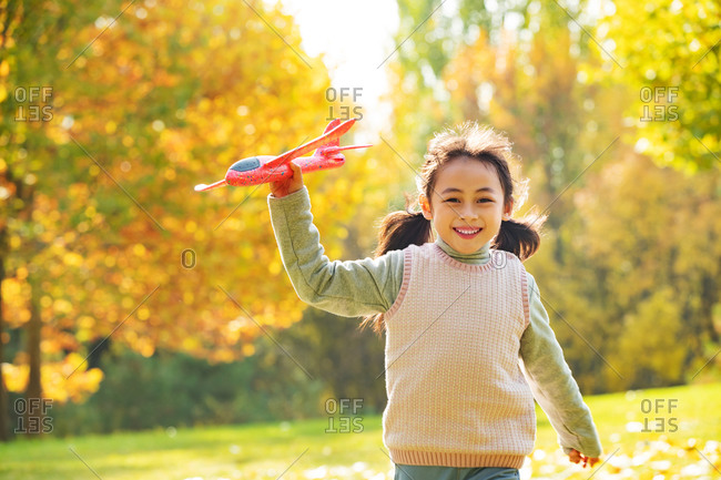 Young girl playing with a toy plane in the park