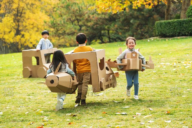 Children playing with planes and cars made out of cardboard