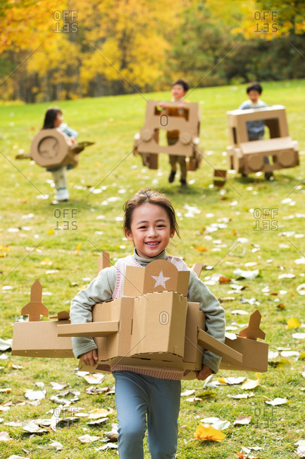 Happy children play with planes and cars made out of cardboard
