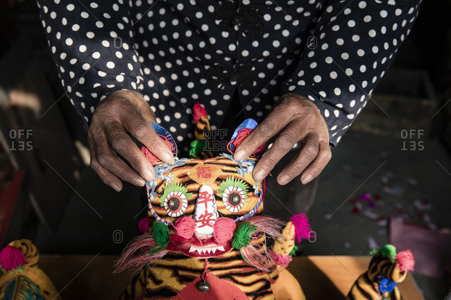 January 8, 2018: Hand holding a tiger made out of fabric