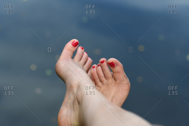 Woman's feet crossed with red toenail polis