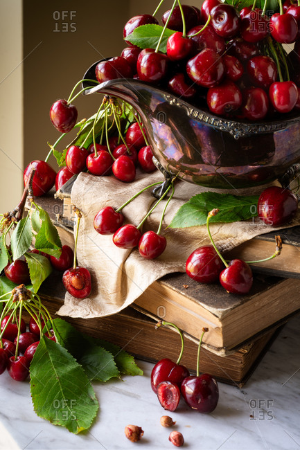 Close up still life of cherries in a shiny gravy boat on a stack of books