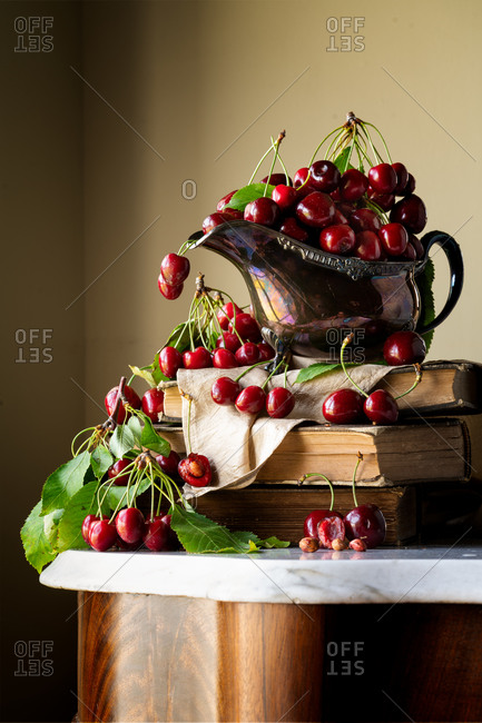 Still life of cherries in a shiny gravy boat on a stack of books