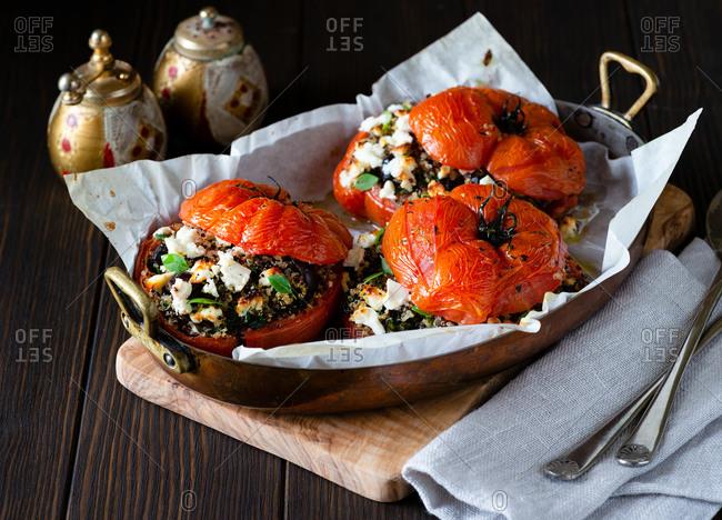 Quinoa with kalamata olives and feta cheese stuffed tomatoes in baking dish