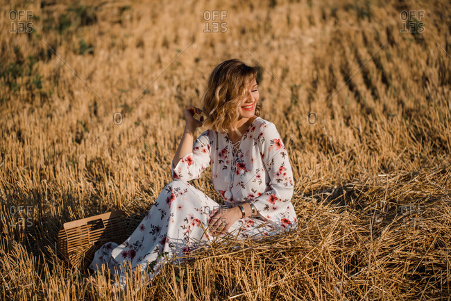 Woman wearing floral dress sitting beside a wooden purse in a hay field and smiling