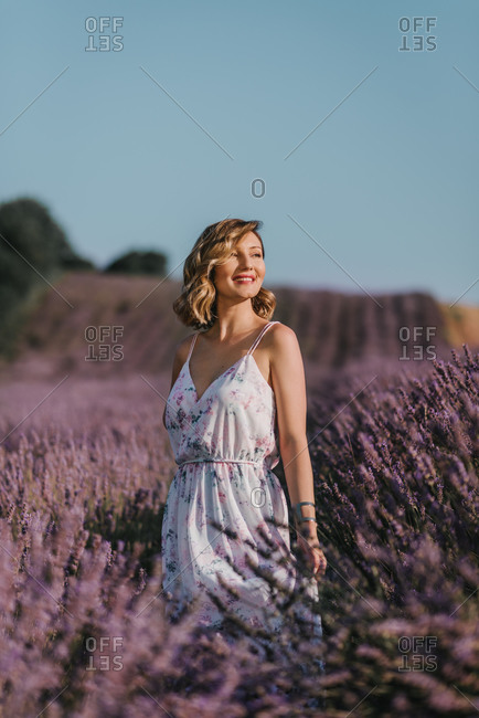 Young woman standing between violet lavender field in Europe