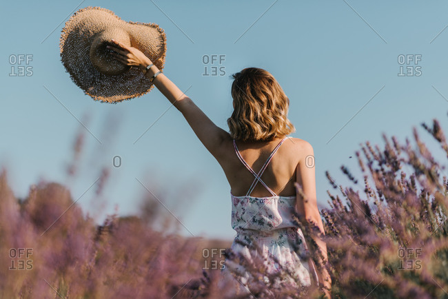 Young woman in a floral dress holding straw hat in the air in lavender field