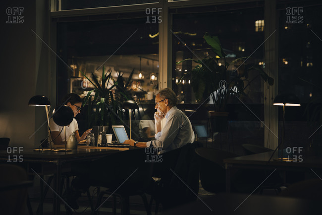 Male and female professionals working late in dark office at night