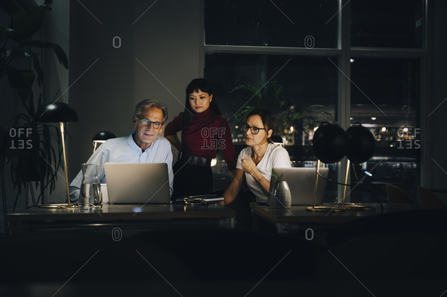 Senior businessman planning strategy with female colleagues at coworking space in dark