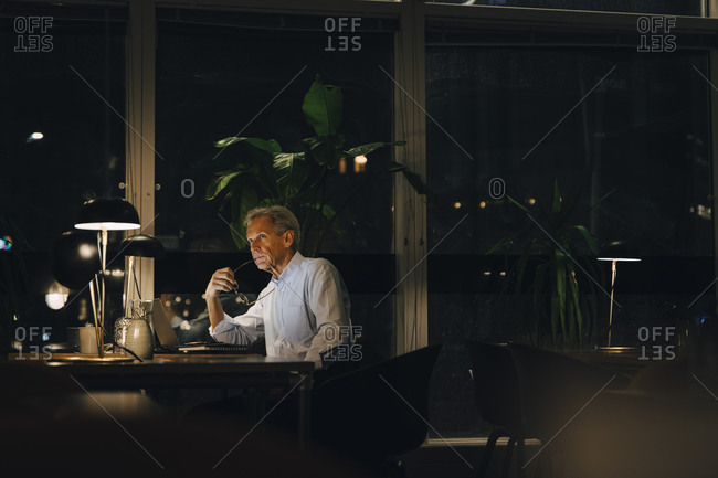 Thoughtful senior male professional looking away while sitting at desk in dark office