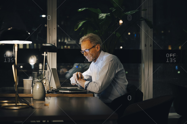 Dedicated senior male professional working late at creative workplace
