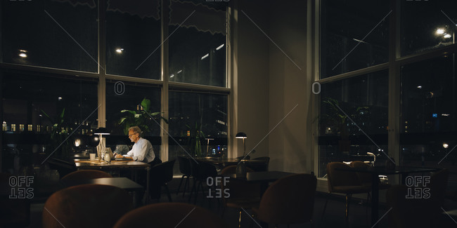 Determined senior businessman working late in dark office at night