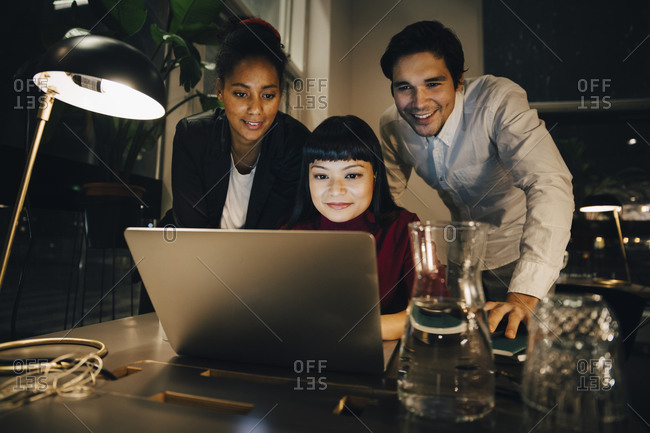 Smiling business colleagues planning strategy over laptop while working late at creative office