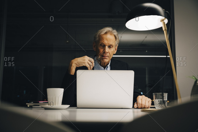 Dedicated senior male entrepreneur looking at laptop while working late in creative workplace