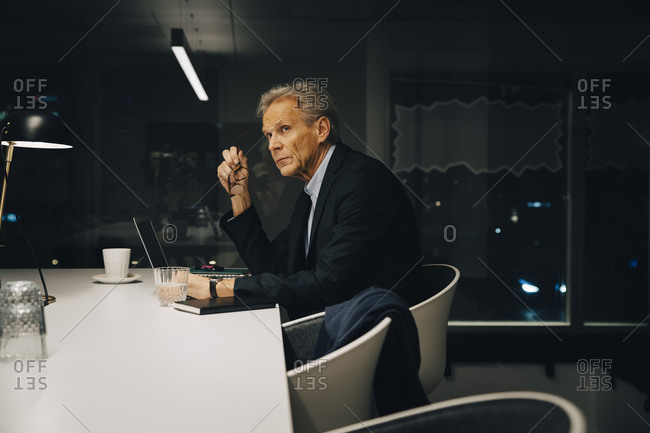 Side view of thoughtful senior male professional looking away while sitting with laptop at illuminated desk working late