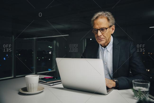Confident senior businessman using laptop while sitting at illuminated desk in creative office