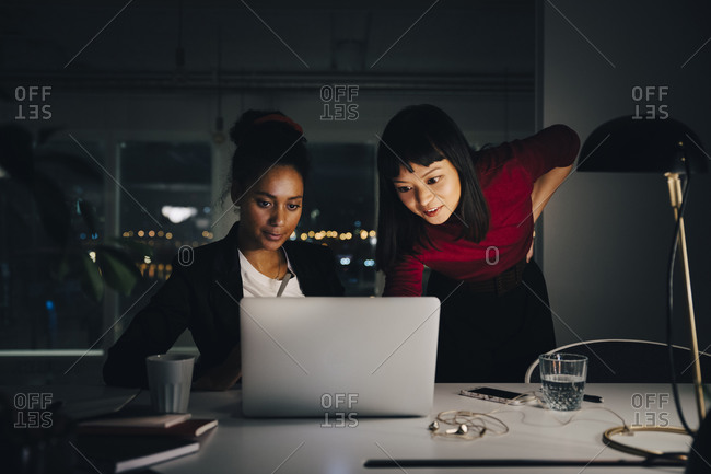 Confident female business colleagues discussing over laptop while working late at creative office