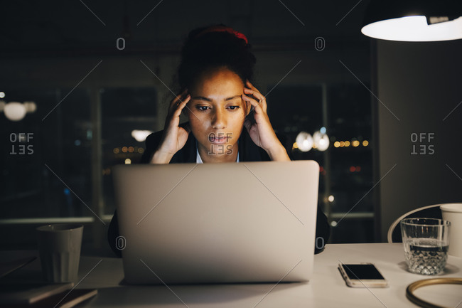 Young female entrepreneur with headache while working late in office