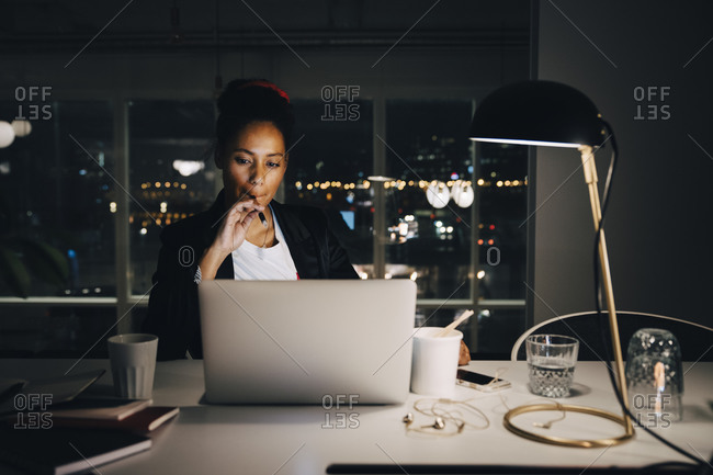 Determined female professional looking at laptop while sitting and working late in coworking space