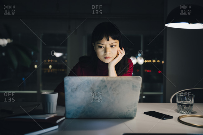 Dedicated young businesswoman with hand on chin using laptop while working late at office