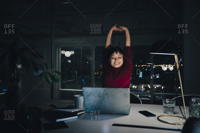 Smiling young businesswoman stretching while working late in coworking space